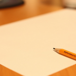 Blank piece of paper and pencil on a wooden desk.